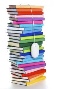 Computer mouse hanging from top of rainbow-colored book stack